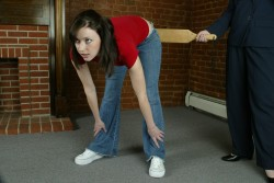 Donna from Realspankings.com has that look on her face that comes from knowing that the large wooden paddle is about to be applied to her bottom.